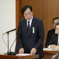 Deep remorse: Mizuho Financial Group President Yasuhiro Sato (left) addresses the Committee on Financial Affairs of the Lower House in Tokyo on Wednesday | KYODO