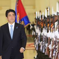 ASEAN sweep: Prime Minister Shinzo Abe reviews an honor guard at Peace Palace in Phnom Penh on Saturday. Abe traveled to Laos on Sunday for the second and final leg of a two-day trip to Southeast Asia that has seen him visit all 10 members of the Association of Southeast Asian nations in less than a year since he took office | AP