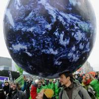 The world is ours: Activists march to campaign against global warming Saturday in Warsaw, where a United Nations conference is discussing a new climate deal | AP/KYODO