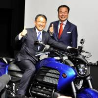 Cross-over rivals: Toyota Motor Corp. President Akio Toyoda (left) makes a surprise visit to the Honda Motor Co. booth where Honda President and CEO Takanobu Ito was appearing during the Wednesday media preview of the Tokyo Motor Show. The biannual event at Tokyo Big Sight will open to the public Saturday.  | YOSHIAKI MIURA
