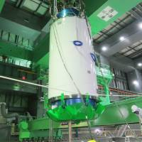 Risky business: A special transport cask for removing nuclear fuel assemblies is moved inside the building housing reactor 4 at the Fukushima No. 1 power plant Monday.   TEPCO/KYODO