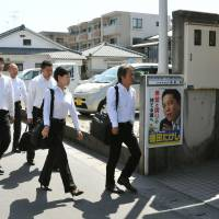 Knock, knock: Investigators from the Tokyo Prosecutor's Office enter the Kagoshima home of Torao Tokuda, father of Liberal Democratic Party lawmaker Takeshi Tokuda and founder of the Tokushukai hospital and welfare chain, on Tuesday | KYODO