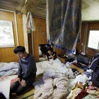 Taking a break: Chinese trainees Li Jin (left) and Wang Xile sit in a room at their dormitory in Hokota, Ibaraki Prefecture, in May. Critics say the training program is being abused by employers who view it as a source of cheap labor. | AP