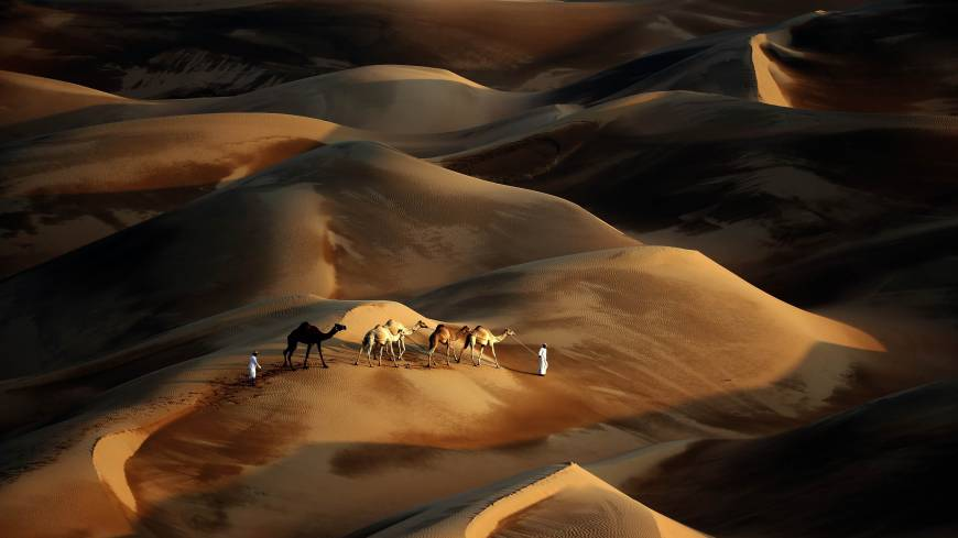 Trackless sands: Tribesmen cross the Liwa Desert, over 200 km southwest of Abu Dhabi, on Saturday. At U.N. climate talks in Warsaw, negotiators adopted a 'loss and damage mechanism' to aid countries threatened by extreme climate calamities.   AFP-JIJI