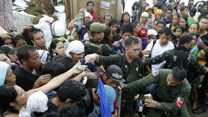 Working class passengers: Typhoon survivors jostle for a chance to board a C-130 military transport plane Tuesday in the central Philippine city of Tacloban. Thousands swarmed the airport Tuesday seeking a flight out, but only a few hundred made it | AP
