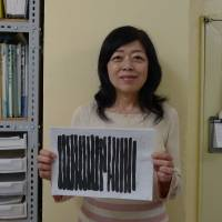 Redacted: At the Hoshino Defense Committee office in Tokyo, Akiko Hoshino holds up a letter from her husband that was blacked out by prison authorities. | WILLIAM ANDREWS