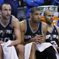 Helpless bystanders: San Antonio's (from left) Manu Ginobili, Tim Duncan and Tony Parker watch from the bench during the fourth quarter of the Spurs' 94-88 loss to the Thunder on Wednesday.   AP