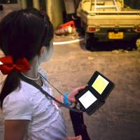 Play along: Using the Nintendo DS game console provided, participants answer questions about what to do after a quake. | JASON JENKINS