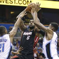 Can't touch this: Miami's LeBron James shoots while being guarded by Orlando's Maurice Harkless and Solomon Jones during the Heat's 120-92 win on Wednesday. | AP