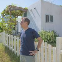 The island life: Keith Gordon stands outside his home in Kunigami in northern Okinawa.  The grounds are spacious enough to accommodate a kitchen garden, home music studio and patio area.   STEPHEN MANSFIELD