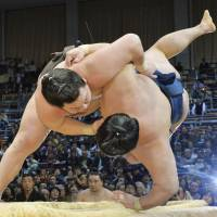 Hit the deck: Hakuho (left) takes Goeido on the 12th day of the Kyushu Grand Sumo Tournament.   KYODO