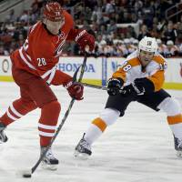 Hacked: Carolina's Alexander Semin shoots as Philadelphia's Adam Hall defends in the second period on Tuesday night. The Hurricanes edged the Flyers 2-1 in overtime | AP