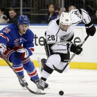 Coast to coast: New York's Chris Kreider (left) competes with Los Angeles' Jarret Stoll during the Kings' 1-0 win on Sunday.   AP