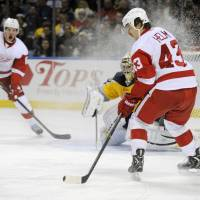 Hit me, I'm open: The Red Wings' Darren Helm (right) collects a pass from Justin Abdelkader (left) as Sabres' goalie Ryan Miller watches on Sunday in Buffalo, New York. | AP
