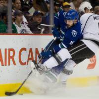 Detour: Los Angeles' Jake Muzzin checks Vancouver's Brad Richardson into the boards in the first period on Monday night. | AP