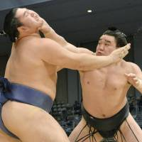 Get a grip: Harumafuji (right) holds Tochinokawa at bay at the Kyushu Grand Sumo Tournament in Fukuoka on Monday. | KYODO