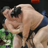 One still unbeaten: Hakuho (left) outmuscles ozeki Kakuryu in the raised ring on Friday at the Kyushu Grand Sumo Tournament. Hakuho improved to 13-0.  | KYODO