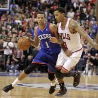Shoulder to shoulder: Philadelphia's Michael Carter-Williams (left) moves the ball as Chicago's Derrick Rose defends during the Sixers' 107-104 win on Saturday   AP