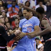 This is a stick-up: Bulls defenders Kirk Hinrich (left) and Nazr Mohammed (right) try to take the ball away from Ryan Hollins on Sunday in Los Angeles. The Clippers won 121-82. | AP