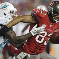 Get off me: Buccaneers receiver Vincent Jackson slips out of a tackle during Tampa's game against Miami on Monday night. The Buccaneers won 22-19 | AP