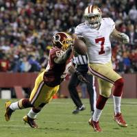 Elusive: San Francisco QB Colin Kaepernick scrambles away from Washington's Perry Riley in the first half on Monday night. | AP
