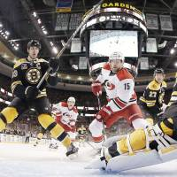 Drawing a crowd: Bruins defenseman Zdeno Chara (left) and the Hurricanes' Tuomo Ruutu skate in front of Boston goalie Chad Johnson on Sunday. The Bruins won 3-2 in overtime. | AP