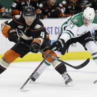 Too late: Anaheim's Cam Fowler (left) passes the puck as Dallas' Valeri Nichushkin defends in the first period on Monday.   AP