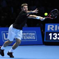 Opens with win: Stanislas Wawrinka plays a shot from Tomas Berdych in their round-robin match at the ATP Finals on Monday | AFP-JIJI