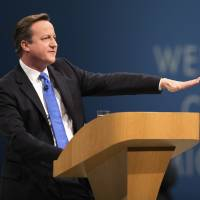 Calm Cameron: British Prime Minister David Cameron, addresses delegates at the Conservative Party's annual conference in Manchester, England, on Oct. 2. Cameron has urged 'sensible and calm language' on the Roma issue | BLOOMBERG