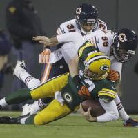Painful play: Green Bay QB Aaron Rodgers is sacked by Chicago's Shea McClellin (middle) and Isaiah Frey on Monday night | AP