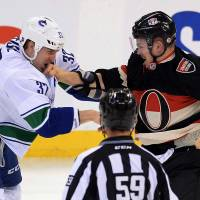 Right on the kisser: Ottawa's Mark Borokwiecki lands a punch to the face of Vancouver's Dale Weise in the first period on Thursday night. The Canucks beat the Senators 5-2. | AP