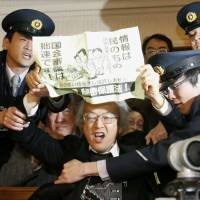 Paper trail: Guards at the Diet building restrain a man who opposes the ruling coalition's moves to force its contentious state secrets bill through the Lower House on Tuesday. | KYODO