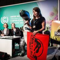 Heated moment: A member of the activist group Climate Action Network announces Friday at climate talks in Warsaw that Japan was being given the Fossil of the Day Award for slashing its goal for reducing greenhouse gas emissions. | AFP-JIJI