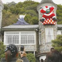 Up on the housetop: Visitors to the Uroko Museum of Art, a converted home in a Kobe district packed with Western-style residences, known as 'ijinkan,' take photos of a mock Mount Fuji and Santa Claus on Wednesday. | KYODO