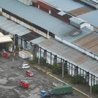 Aftermath: Fire engines and other emergency vehicles sit out in front of the factory at the Nippon Steel and Sumitomo Metal Corp. Yahata plant in Fukuoka Prefecture on Monday, where an explosion killed one worker and injured two others. | KYODO