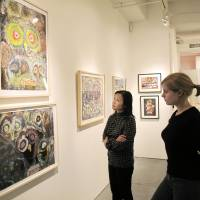 Bird's-eye view: Midori Kano (left), assistant director of Cavin-Morris Gallery in New York, and a visitor view owl-themed paintings by disabled artists from countries including Japan, Nepal, South Korea and Italy on Oct | 23 DURING AN EXHIBITION TITLED 'FUKURO: OWLS OF HAYASHIBARA, JAPAN.'  KYODO