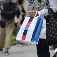 Ready to spend: A woman with an Isetan Mitsukoshi bag strolls through the upscale Ginza shopping district in Tokyo | BLOOMBERG