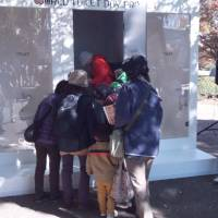 Luxury for many: Curious onlookers look at toilet stalls placed in Tokyo's Showa Kinen Park Tuesday, as UNICEF celebrates World Toilet Day. The one in the center had no toilet to raise awareness of the lack of basic sanitation in many parts of the world. | TOMOHIRO OSAKI