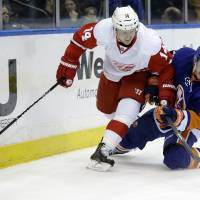 That's mine: Red Wings center Gustav Nyquist (left) and Islanders defenseman Thomas Hickey chase the puck on Friday. | AP
