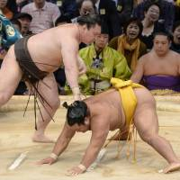 Rolling along: Yokozuna Hakuho reminds Shohozan of his prowess in the raised ring on Saturday at the Kyushu Grand Sumo Tournament | KYODO