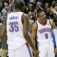 All or nothing: Thunder guard Russell Westbrook (right) celebrates with Kevin Durant after hitting the game-winning shot in OT on Friday.   AP