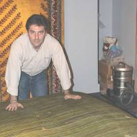 Flying high: Ali Farmani, manager of a store that sells Gabbeh carpets in Tehran, spreads out some rugs that were woven by Qashqai women.   KYODO