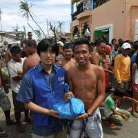 Under the radar: A member of the International Children's Action Network (ICAN) delivers aid to residents in the town of Dulag on typhoon-hit Leyte Island. | COURTESY OF ICAN