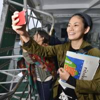 Intrepid: Atsuko Isamoto, founder and editor-in-chief of the Rito Keizai Shimbun website and Ritokei quarterly publication, snaps a photo of Kashiwa Island on Oct. 5 while taking the ferry there from Karatsu, Saga Prefecture. | KYODO