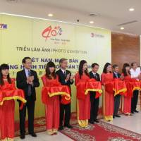 'New Horizon': People involved in a photo exhibition jointly held by the Vietnam News Agency and Kyodo News launch the event Monday in Hanoi | KYODO
