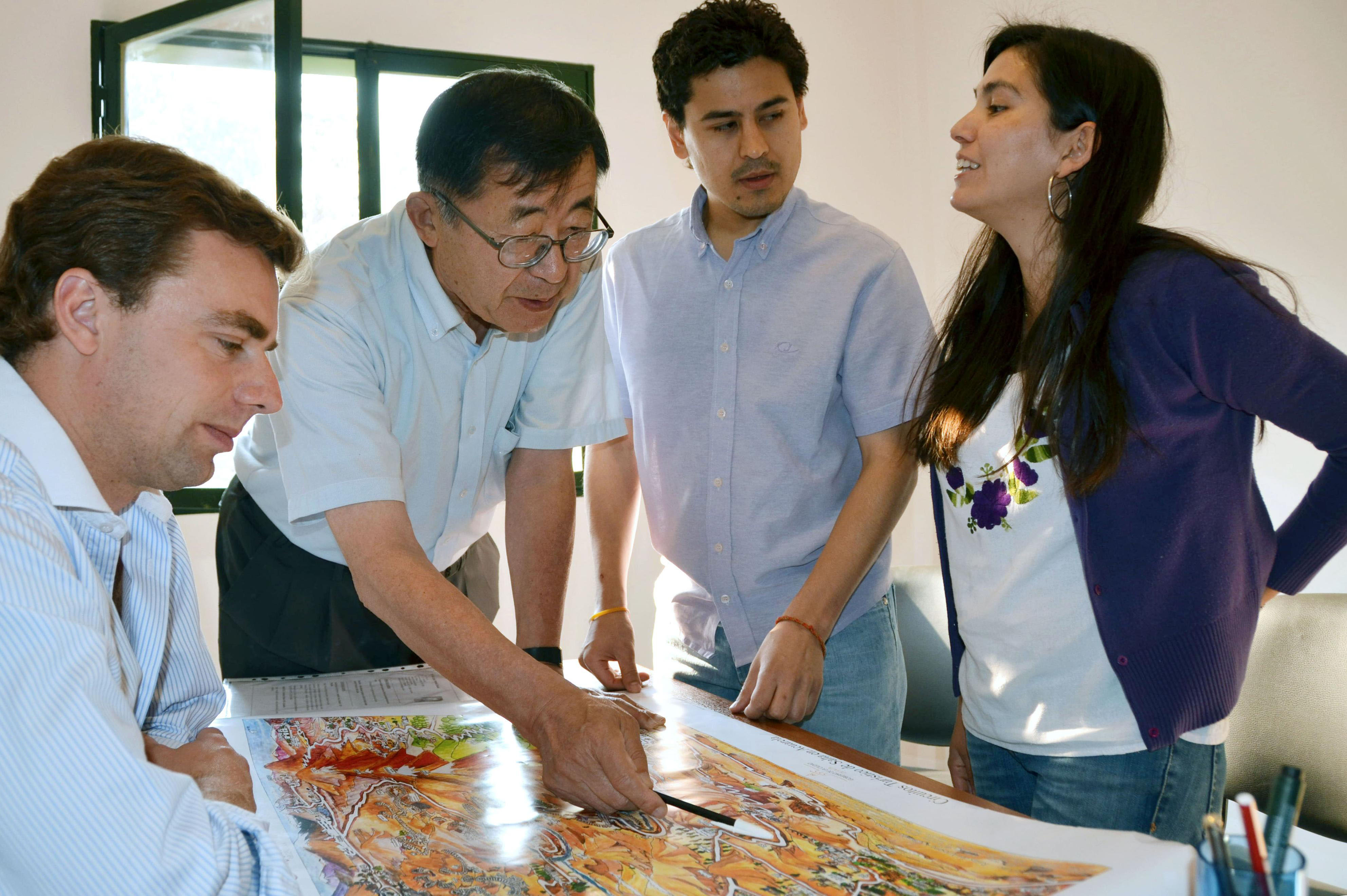 Laying it out: Akitada Oishi (second from left), former mayor of Hita, Oita Prefecture, looks at a local tourist map in the government office of the northern Argentine province of Salta on Sept. 11, together with Salta government employees | KYODO