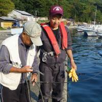 End of the line?: Fishery training program participant Junya Kashiwagi (right) is taught by an experienced fisherman how to tie a knot in Haida, Mie Prefecture. | KYODO