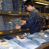 Beyond denim: A manager at G-Star RAW Store Tokyo Shibuya arranges jeans before the shop opens on Nov. 21. An employee from the store took the exam for Japan's first 'jeans sommelier' certification exam earlier this year. | KYODO