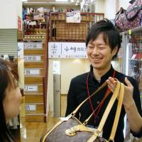 Recycler: Junichi Kato, manager of the Tifana outlet in the Musashikoyama district in Tokyo, helps a customer Oct. 15 | KYODO