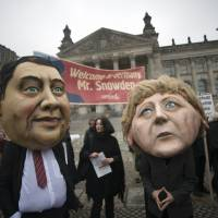 In from the cold: Activists wearing masks of German Chancellor Angela Merkel and the Social Democratic Party Chair Sigmar Gabriel stand in front of a sign welcoming fugitive U.S. whistle-blower Edward Snowden in Berlin on Nov. 18.   AFP-JIJI
